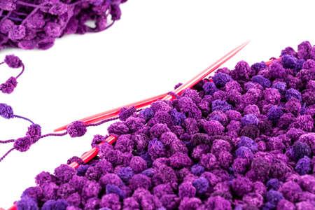 Purple yarn with knitting needles on white background.
