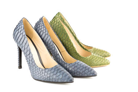 Two pairs of stylish high heels python leather shoes isolated on white background.