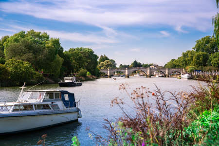 Thames riverfront with many boats and bridge in Richmond, London, UK. Stock Photo