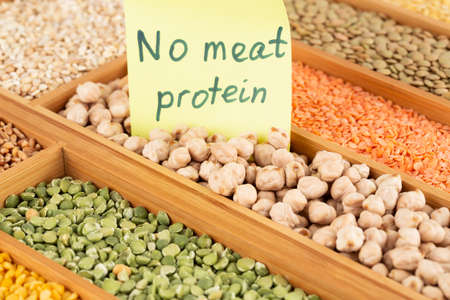 The collection of different groats, chickpeas, peas, wheat and lentils in the wooden box with notice no meat protein.