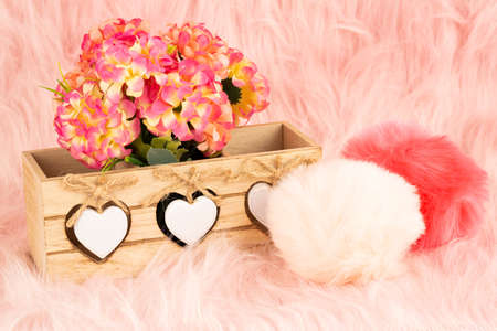 Beige wooden box, flowers and fluffy pompons on pink fur background.