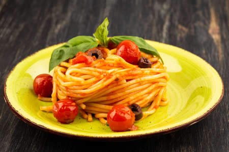 Pasta spaghetti Napoli or Napolitana on green plate on black background. Italian cuisine.