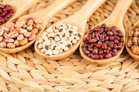 Various beans in the wooden spoons on the beige background.