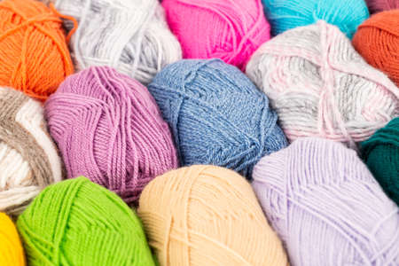 The stack of colorful knitting yarn clews close up picture.