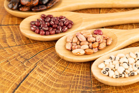 Various beans in the wooden spoons on the brown background.