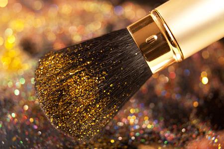 brilliancy: Close-up on brush and gold shining powder. Studio shot. Stock Photo