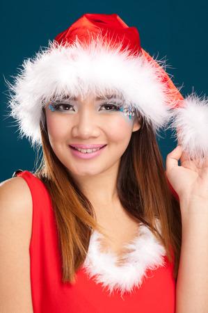 Beautiful christmas woman with santa costume. Studio shot. Blue background. photo