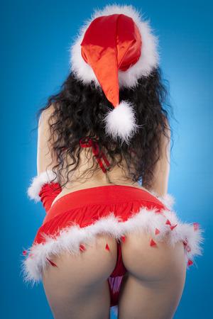 Sexy santa helper. Red lingerie, hat and gloves. Studio shot. Blue background photo