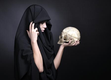 cranium: Woman holding a human cranium. Covered with black cloth.
