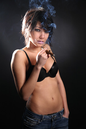 Sexy brunette woman with black bra smoking cigar photo