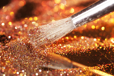 Close-up on makeup brush and gold shining powder photo