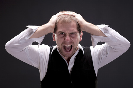 Portrait of young angry screaming man with a suit. Studio shot.  Black background photo
