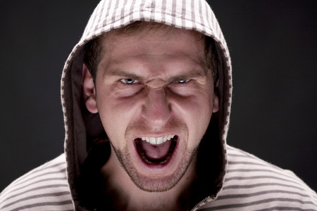 Portrait of young angry screaming man with a hood. Studio shot.  Black background photo