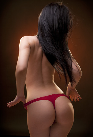 Beautiful woman body in the back with long hair. Studio shot. Black background. Stock Photo