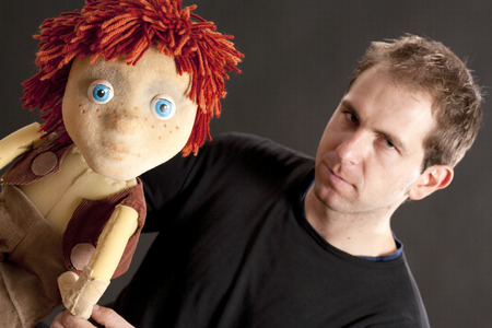 puppetry: Portrait of a actor and puppet. Studio shot. Black background Stock Photo