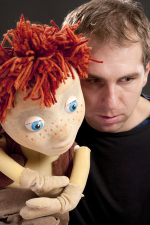 gesticulate: Portrait of a actor and puppet. Studio shot. Black background Stock Photo