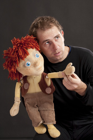 Portrait of a actor and puppet. Studio shot. Black background photo