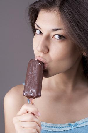 Sexy brunette woman eating chocolate ice cream. Studio shot photo