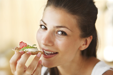 Young happy woman eating sandwich with tomatoes, cheese and basil. photo