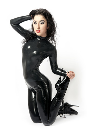 Sexy flexible brunette in black latex and boots whit high heels. Studio shot. White background. photo