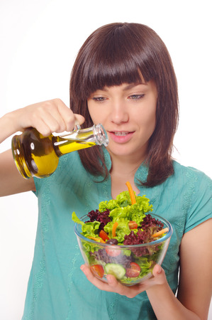 Young happy woman making salad with vegetables and oil. Studio shot. On white background photo
