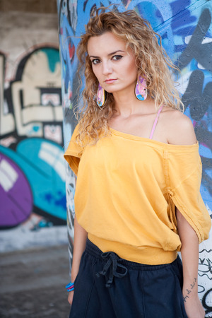 Teenage hip blond girl standing on front of graffiti wall. Outdoor portrait. Stock Photo