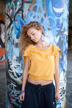 Teenage hip blond girl standing on front of graffiti wall. Outdoor portrait. photo