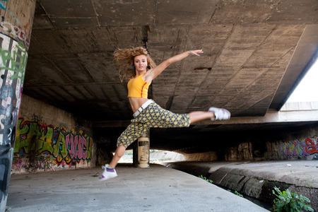 Teenage hip blond girl jumping river photo