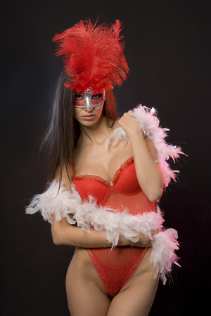 Beautiful sexy woman with red lingerie and mask with feathers. Black background. Studio shot. Stok Fotoğraf