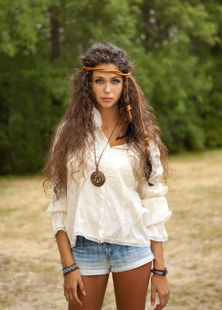 Beautiful hippie girl with ropein hair in the park. Outdoor portrait. photo
