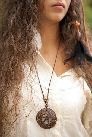 Beautiful hippie girl with medallion in the park. Outdoor portrait. photo