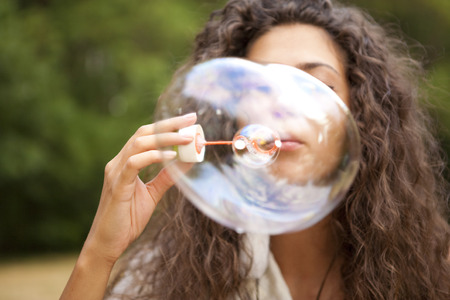 Beautiful woman in the park playing in bubbles cup. Outdoor portrait. photo
