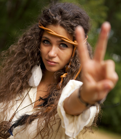 Beautiful hippie girl with rope in the park making the sign of peace. Outdoor portrait.
