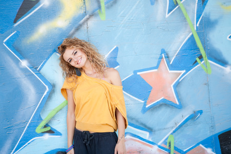 Teenage hip blond girl standing in front of graffiti wall. Outdoor portrait. photo