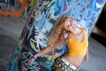 Teenage hip blond girl standing by graffiti wall. Outdoor portrait. photo
