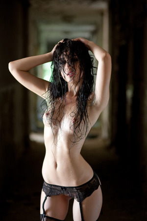 wet breast: Sexy wet woman with black lingerie, stockings in old abandoned building. Stock Photo