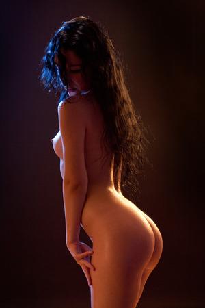 erotic fantasy: Sexy voluptuous brunette woman posing. Studio shot. Black background