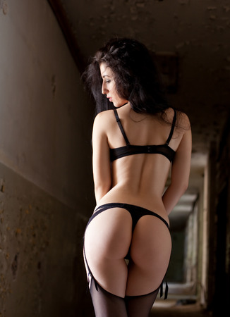 nude woman posing: Sexy brunette woman with black lingerie, stockings in old abandoned building. Stock Photo