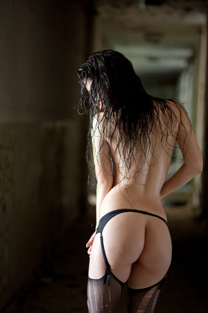 erotic fantasy: Sexy brunette woman with black lingerie, stockings in the back in old abandoned building. Stock Photo