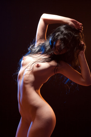 Sexy voluptuous brunette woman posing. Studio shot. Black background