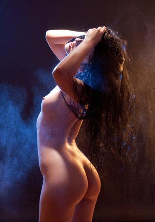 Sexy voluptuous brunette woman posing. Studio shot. Black background