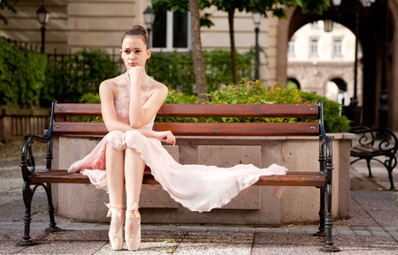 Young beautiful ballerina with pink dress relaxing on bench. Outdoor portrait. photo