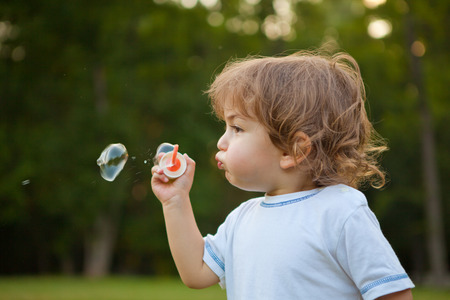 boy long hair: Little boy blowing soap bubbles in park. Outdoor portrait