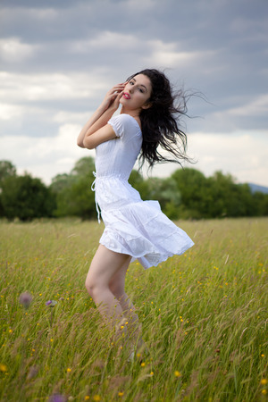 Sexy young woman posing on grass field. Outdoors portrait photo
