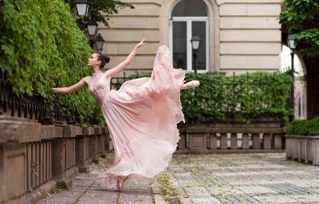 Young beautiful ballerina with pink dress dancing. Outdoor portrait. Stok Fotoğraf