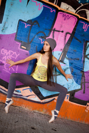 Pretty girl with gray hat in front of graffiti wall dancing ballet. Outdoor portrait. photo