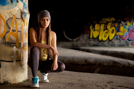 Pretty girl with gray hat in front of graffiti wall. Outdoor portrait. photo