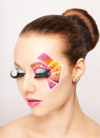 Young woman with fashion makeup using false eyelashes. Studio shot. White background photo