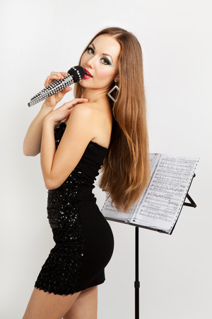 Portrait of a singing beautiful woman in black dress. White background. Studio shot photo