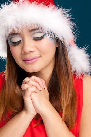 Beautiful christmas woman with santa costume. Studio shot. Blue background photo